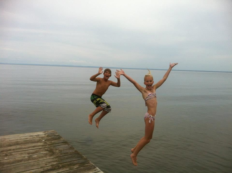 Katie's son and daughter jump off a dock and into a lake