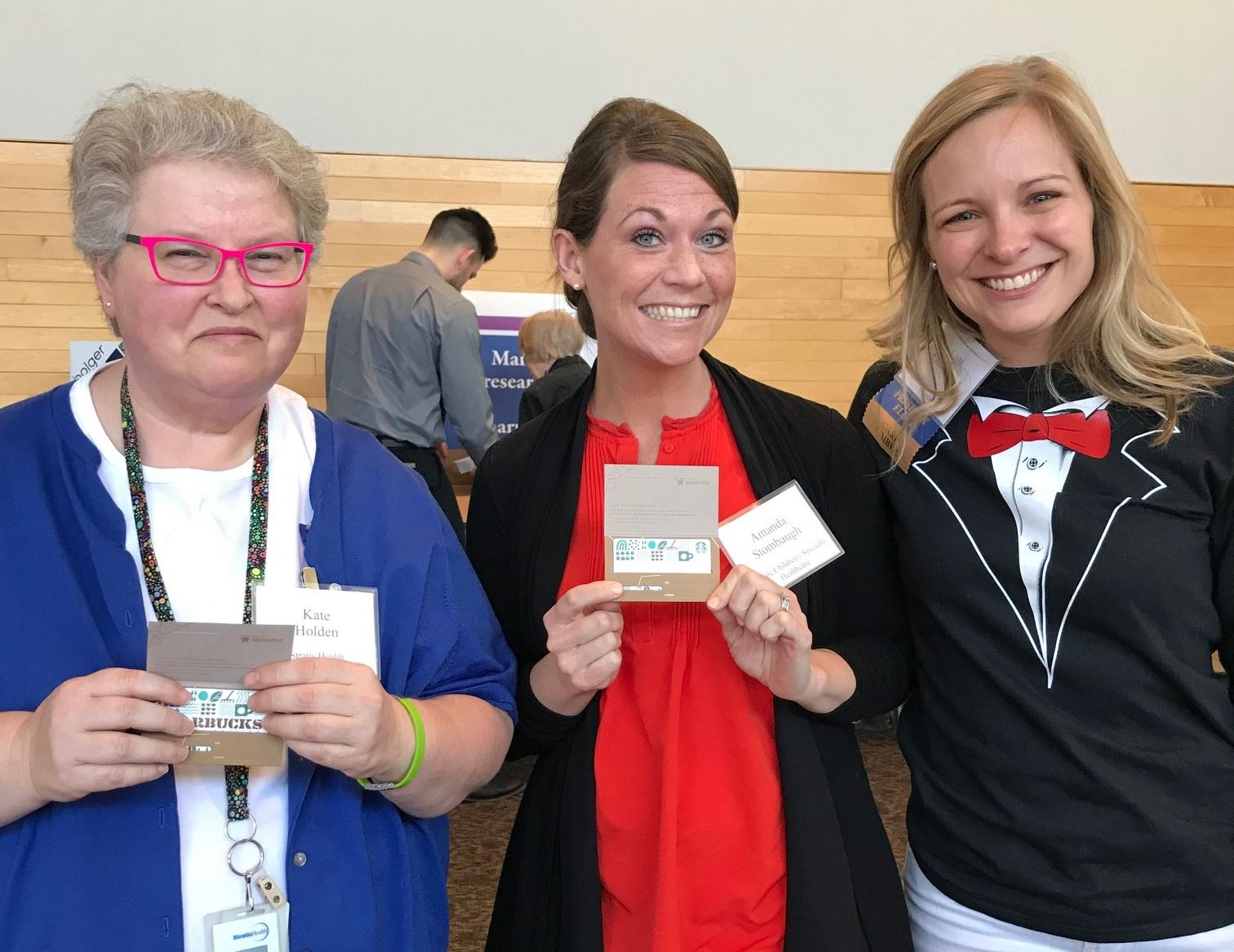 Cassi wears a tuxedo t-shirt as she interacts with two MHSCN members who are showing off some prizes.