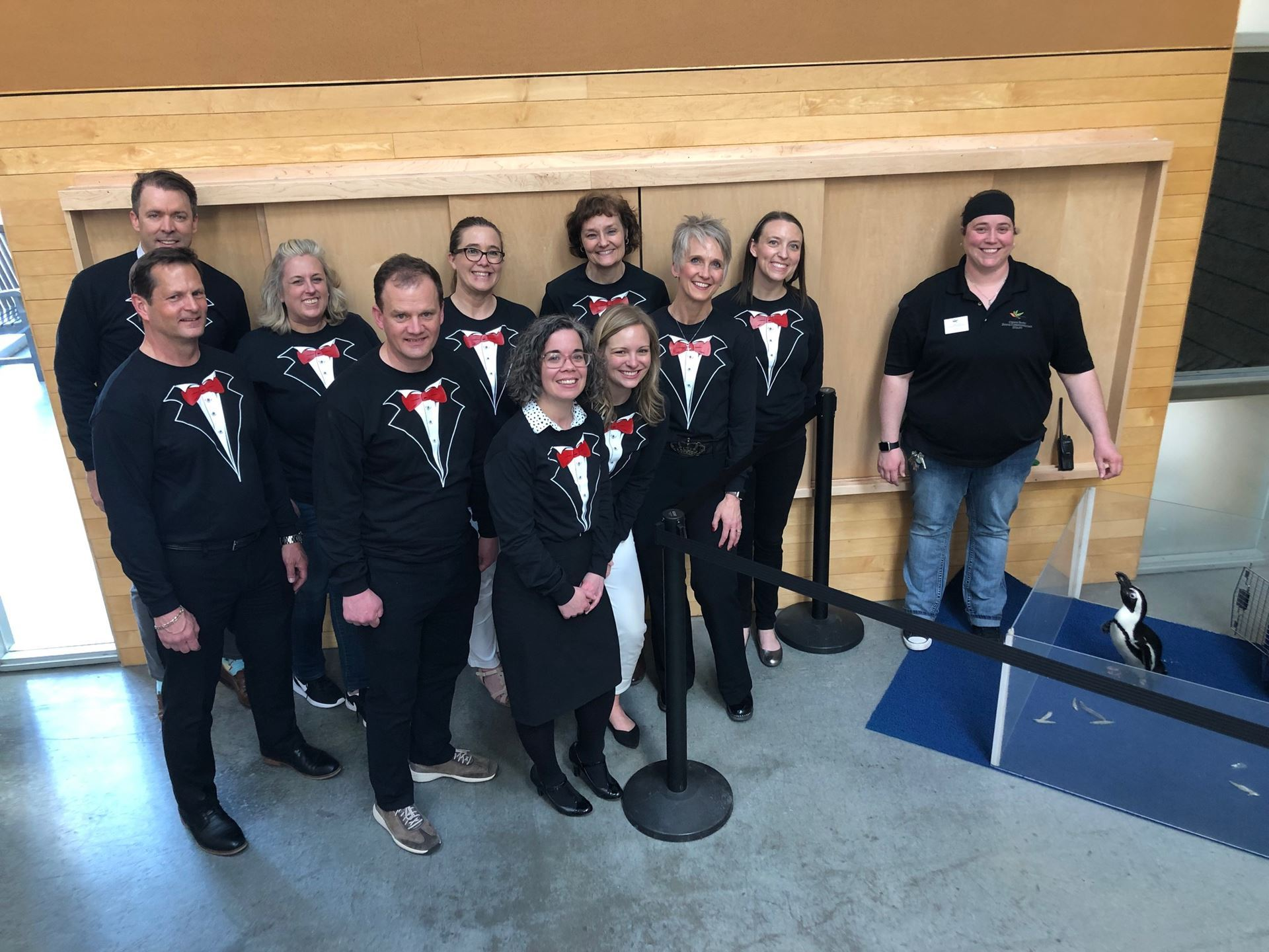 Board members dressed in tuxedos pose next to Cupid the penguin at Como Zoo.